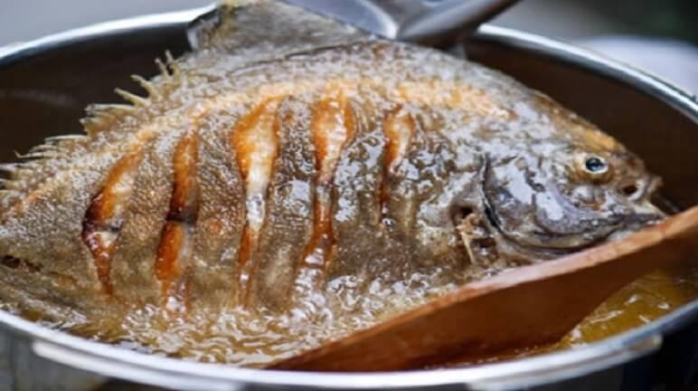 Chiên cá trong chảo ngập dầu.