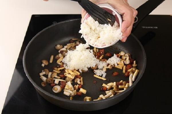 Cơm được cho vào chảo sau khi đã xào sơ lạp xưởng và nấm.